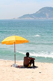 170px-Man_sitting_under_beach_umbrella
