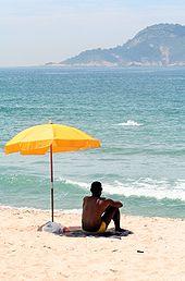 170px-Man_sitting_under_beach_umbrella